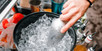 Scooping up ice cubes from a bucket