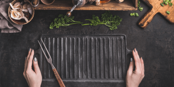 Griddle placed on a table next to an assortment of spices and herbs | Cast Iron Griddle